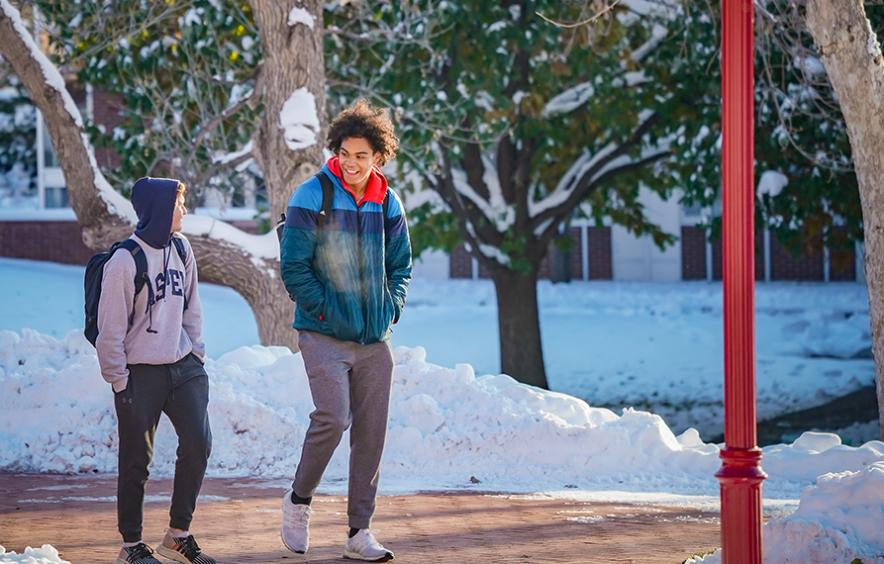 two students walking on campus with snow in background